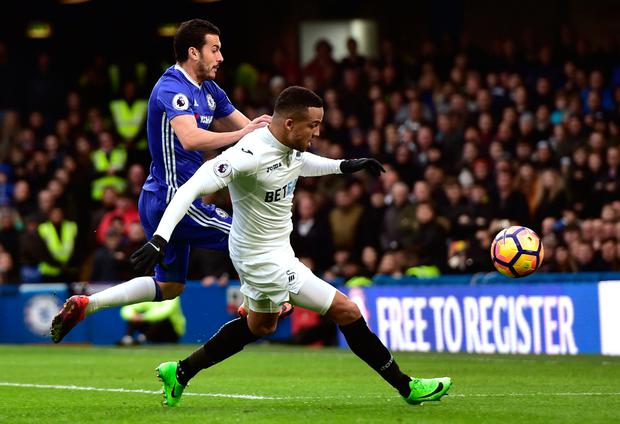 Swansea City's Martin Olsson and Chelsea's Pedro battle for the ball. Photo: PA