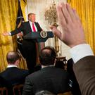 Reporters raise their hands for questions as President Donald Trump speaks during a news conference. Photo: AP