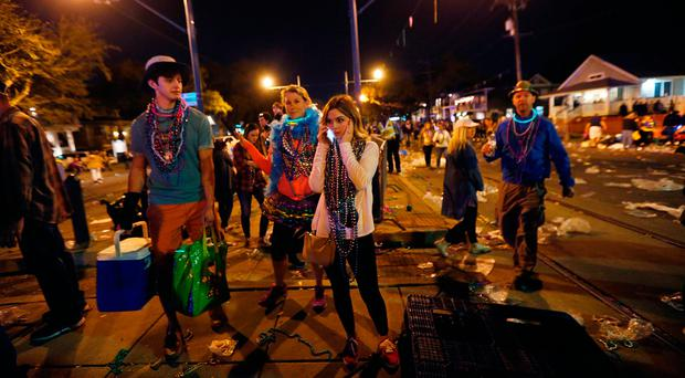 A woman talks on a phone at the scene of where a truck slammed into a crowd and other vehicles, causing multiple injuries, during the Krewe of Endymion parade in New Orleans, Saturday, Feb. 25, 2017. (AP Photo/Gerald Herbert)