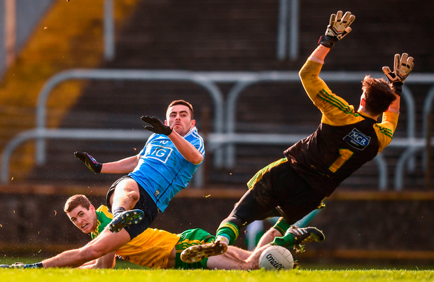 Niall Scully of Dublin shrugs off Donegal's Caolan Ward to slot home his side's goal past goalkeeper Mark Anthony McGinley in Ballybofey yesterday. Photo: Stephen McCarthy/Sportsfile