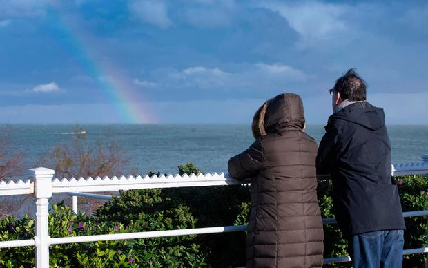 A couple look at a rainbow over Dún Laoghaire harbour. Photo: Fergal Phillips