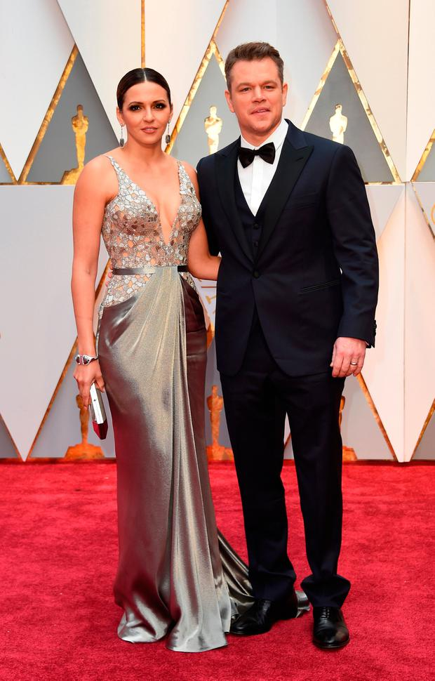 US actor Matt Damon (R) and his wife Luciana Barroso arrive on the red carpet for the 89th Oscars on February 26, 2017 in Hollywood, California. / AFP PHOTO / VALERIE MACONVALERIE MACON/AFP/Getty Images