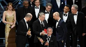 'La La Land' producer Marc Platt speaks with producers Jordan Horowitz (L) and Fred Berger (R) as production staff consult behind them regarding a presentation error of the Best Picture award (later awarded to 'Moonlight'),