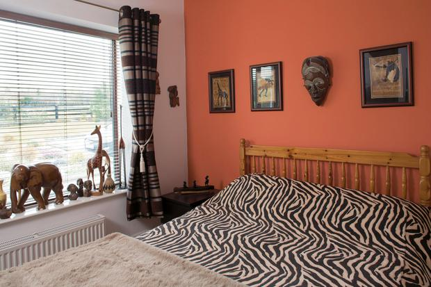 Aengus calls this the guest bedroom, the African room. It's furnished with African prints and carved animals.