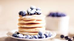 Plate full of pancakes with blueberries as topping