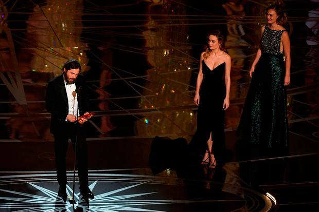 US actor Casey Affleck (L) delivers a speech on stage next to actress Brie Larson (2ndR) after he won the Best Actor award in