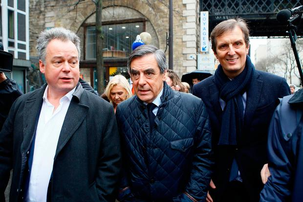 Conservative presidential candidate Francois Fillon, center, leaves his campaign headquarters with his spokesman Jerome Chartier, right, after delivering a speech in Paris, Wednesday, March 1, 2017. (AP Photo/Francois Mori)