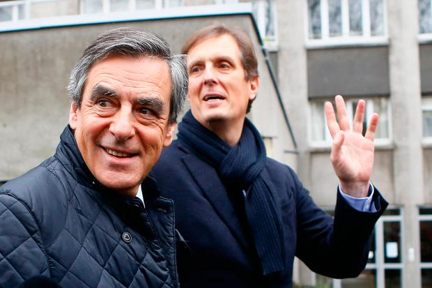 Conservative presidential candidate Francois Fillon, left, leaves his campaign headquarters with his spokesman Jerome Chartier after delivering a speech in Paris, Wednesday, March 1, 2017. (AP Photo/Francois Mori)
