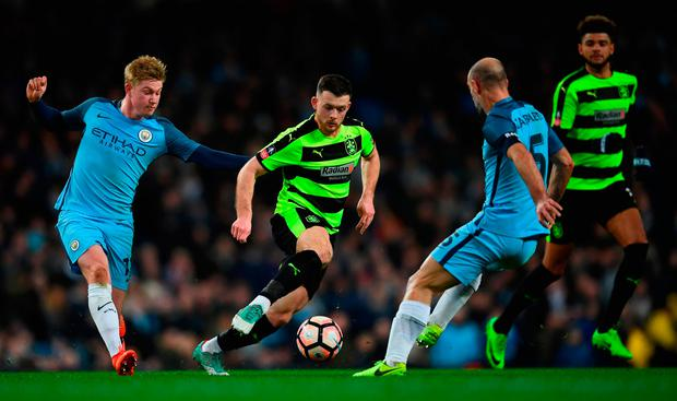 Harry Bunn of Huddersfield Town takes on Kevin De Bruyne (L) and Pablo Zabaleta of Manchester City (Photo by Laurence Griffiths/Getty Images)