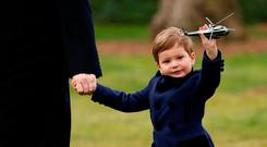 Joseph Kushner holds up a toy Marine One as his grandfather, U.S. President Donald Trump, holds hands with him as they depart aboard Marine One from the White House in Washington, U.S. March 3, 2017. REUTERS/Kevin Lamarque
