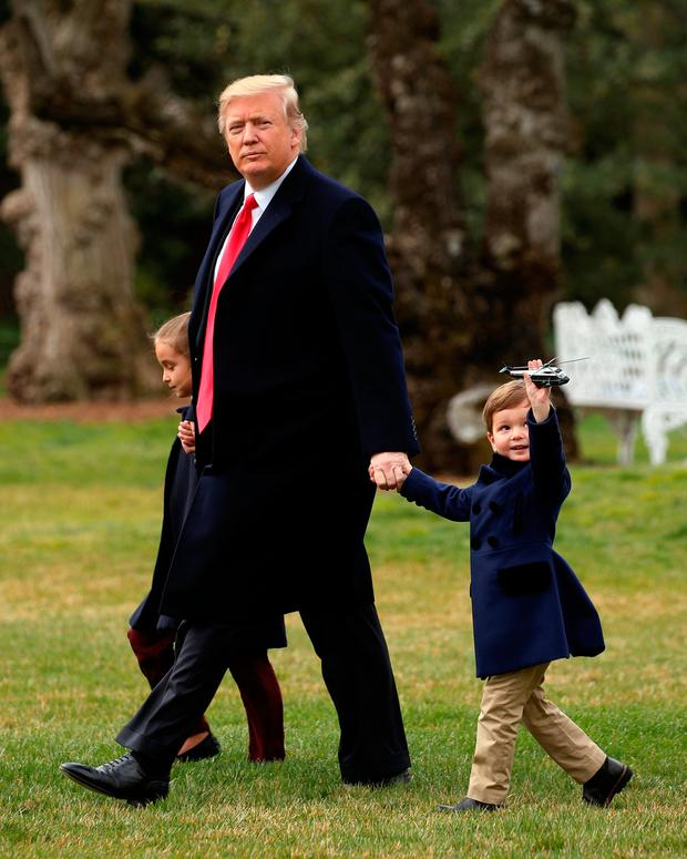 Joseph Kushner holds up a toy Marine One as his grandfather, U.S. President Donald Trump, holds hands with him and his sister Arabella as they depart aboard Marine One from the White House in Washington, U.S. on their way to Florida March 3, 2017. REUTERS/Kevin Lamarque