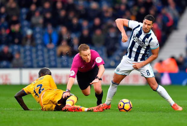 Referee Mike Jones is sent flying having been caught between West Bromwich Albion's Jake Livermore and Crystal Palace's Mamadou Sakho. Photo: PA