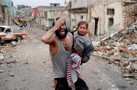 A man cries while he carries his daughter as he walks from Islamic State controlled part of Mosul towards Iraqi special forces soldiers during a battle in Mosul, Iraq, March 4, 2017. Picture taken March 4, 2017. REUTERS/Goran Tomasevic
