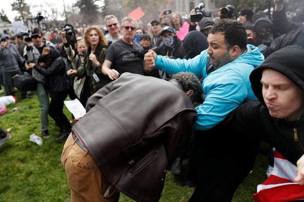 A demonstrator in support of U.S. President Donald Trump (L) scuffles with a counter-protester during a