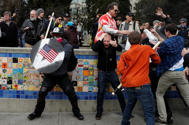 A demonstrator supporting U.S. President Donald Trump (L) holds a shield as a group of men punch a counter demonstrator Photo: REUTERS/Stephen Lam