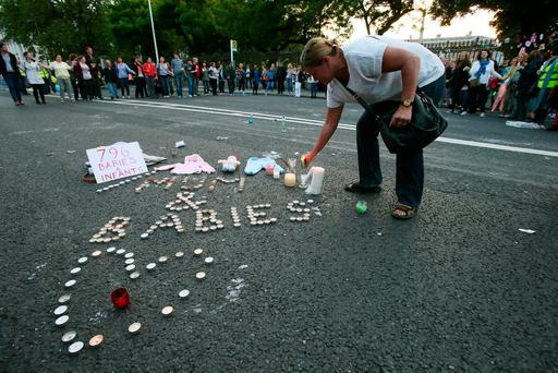 A woman leaves a candle during a 2014 march and candlelit vigil in Dublin, in memory of the Tuam babies. Photo: Brian Lawless/PA