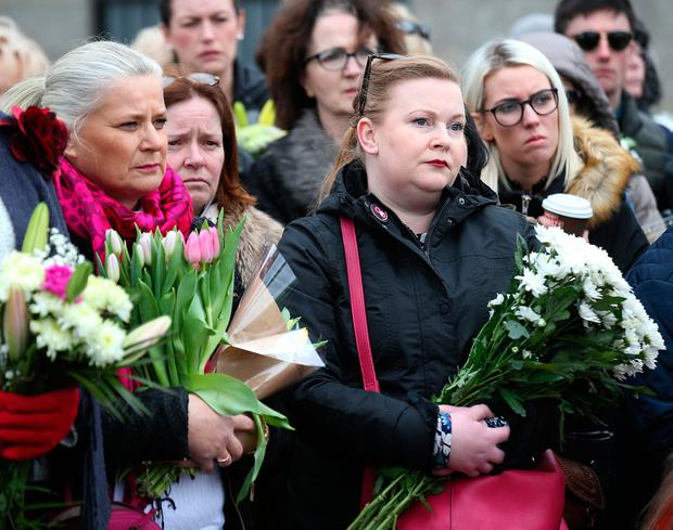 Women holding flowers at the sixth annual Flowers for Magdalenes event in Glasnevin cemetery. Photo: Damien Eagers