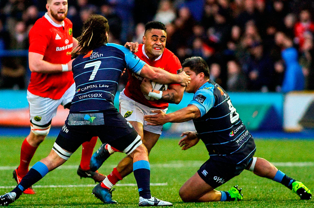 Francis Saili of Munster is tackled by Josh Navidi (left) and Nick Williams of Cardiff Blues Photo: Darren Griffiths/Sportsfile