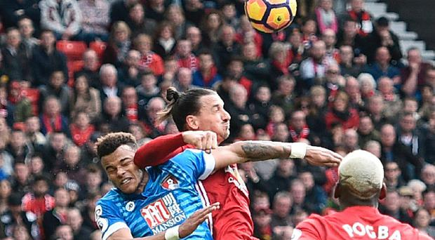 Manchester United's Swedish striker Zlatan Ibrahimovic (C) clashes in the air with Bournemouth's English defender Tyrone Mings (L) during the English Premier League football match between Manchester United and Bournemouth at Old Trafford in Manchester, north west England, on March 4, 2017. / AFP PHOTO / Oli SCARFF