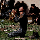 A member of the Iraqi police prays as Iraqi forces clash with Isil fighters in Mosul. Photo: Getty/AFP