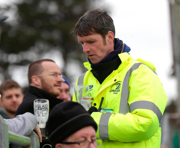 A security guard removes pints at the cup game. Photo: Damien Eagers