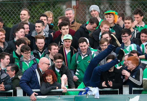 A supporter jumps back into the crowd after running on the pitch. Photo: Damien Eagers