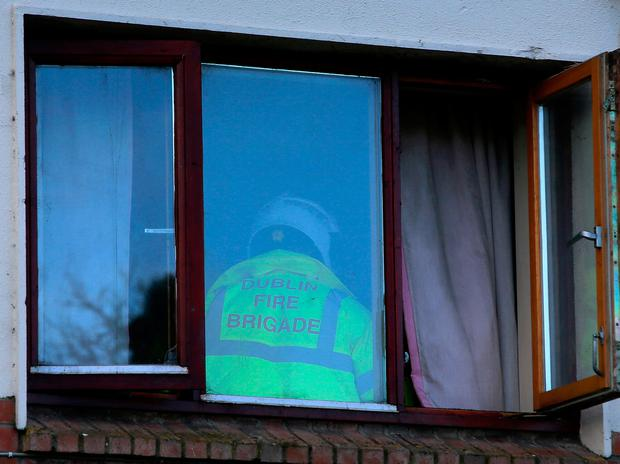 A member of Dublin Fire Brigade inside the apartment where four people lost their lives. Photo: Frank McGrath