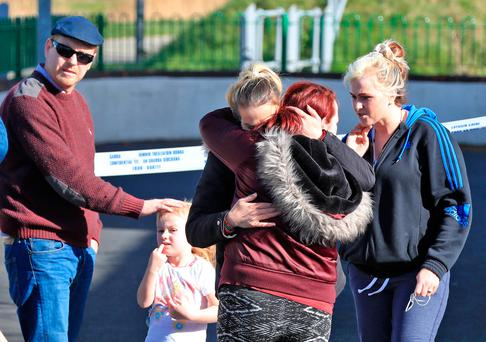 Mourners grieve at the scene of an apartment fire in Clondalkin. Photo: Collins Dublin.