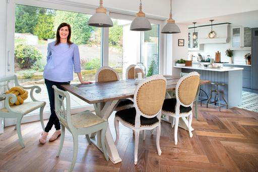 Emma in the dining area. She used to live in Arizona, and she bought the table there - it used to be a barn door. The chairs are from a shop called Willow, also in Arizona. The lamps over the table are from Andy Thornton. Photo: Tony Gavin