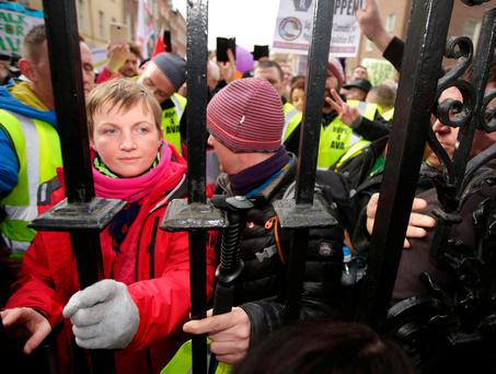 Vera Twomey places her hands on the gates of Dail Eireann following completion of her protest march from Cork in support of the Cannabis for Medicinal Use Regualation Bill. Photo: Gerry Mooney