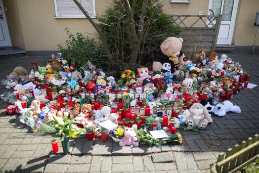 Candles, flowers and stuffed animals have been placed in front of the home of the murdered 9-year-old boy in Herne, Germany (Marcel Kusch/dpa via AP)