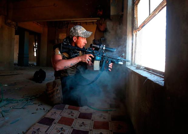 A fighter from Iraq's elite Counter-Terrorism Service takes cover inside a building in Shuhada, west Mosul. Photo: Getty Images