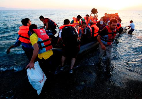 Migrants and refugees in a rubber dinghy arriving on the beach at Psalidi near Kos, Greece. Photo: PA Wire