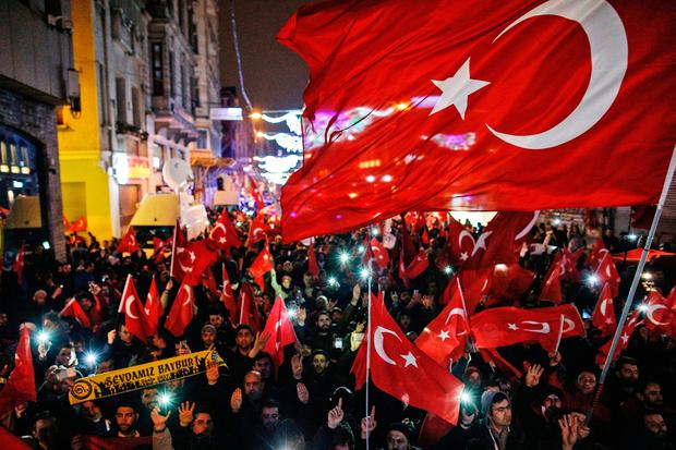 Protesters wave flags outside the Dutch consulate in central Istanbul's Istiklal Avenue, the main shopping road of Istanbul, early Sunday (AP Photo/Emrah Gurel)