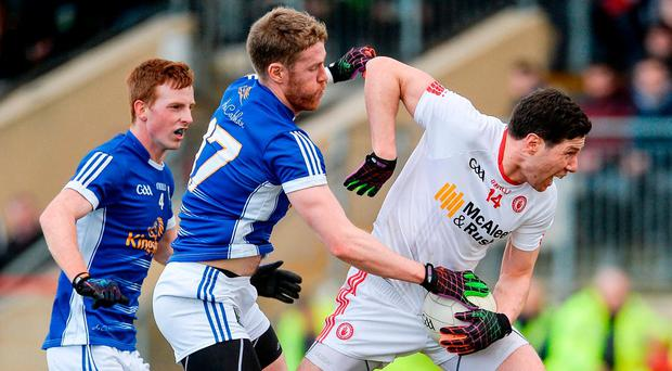 Cavan's Rory Dunne attempts to dispossess Tyrone's Sean Cavanagh. Photo: OLIVER McVEIGH/SPORTSFILE
