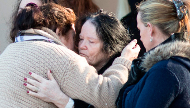 Grandparents of the children who died in the Clondalkin blaze, John and Bridie O'Brien (black coat, centre) are consoled at the removal of their grandchildren's remains yesterday Picture: Mark Condren