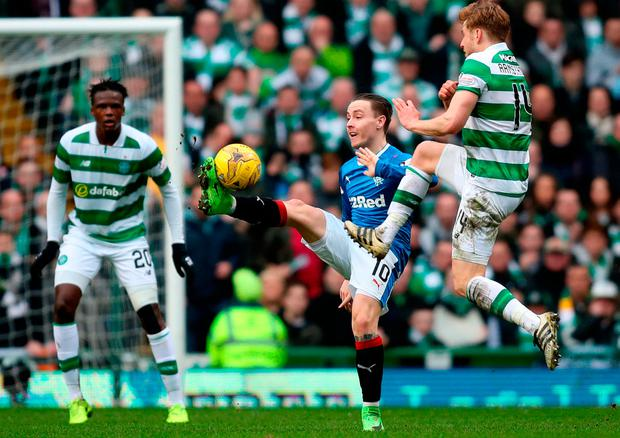 Celtic's Stuart Armstrong (right) and Rangers' Barrie McKay battle for the ball. Photo: Jane Barlow/PA Wire