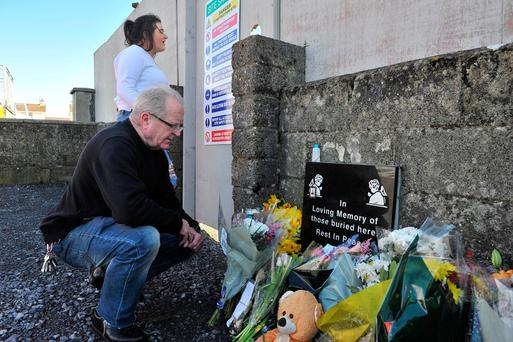 Ivan Hyde, from Limerick, pays his respects at the site of the Tuam Mother and Baby Home while his daughter Lucia looks on. Photo: Ray Ryan