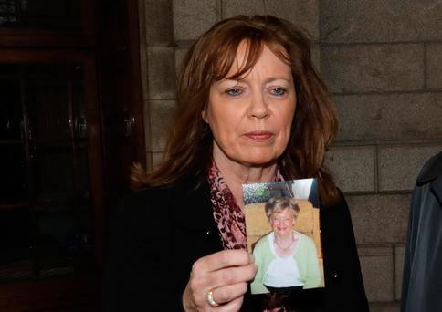 Geraldine Eaton from Templeogue, Dublin pictured leaving the Four Courts holding a photograph of her late mum, Leticia Lawlor - after a High Court action for damages (Image: Collins Courts)