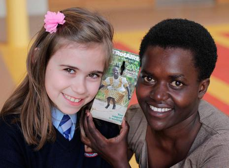St Colmcille's student Lucia Conroy Garcia (8) with Josiane Umumarashavu from Rwanda and the Trócaire box from 2004 with Josiane's photo on the front Photo: Mark Stedman