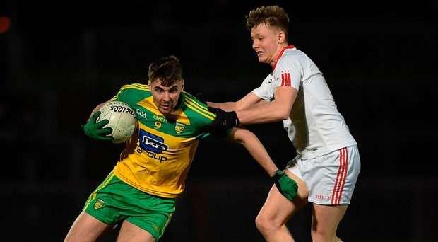 Michael Carroll of Donegal attempts to power past Fergal Meenagh of Tyrone. Photo: Philip Fitzpatrick/Sportsfile