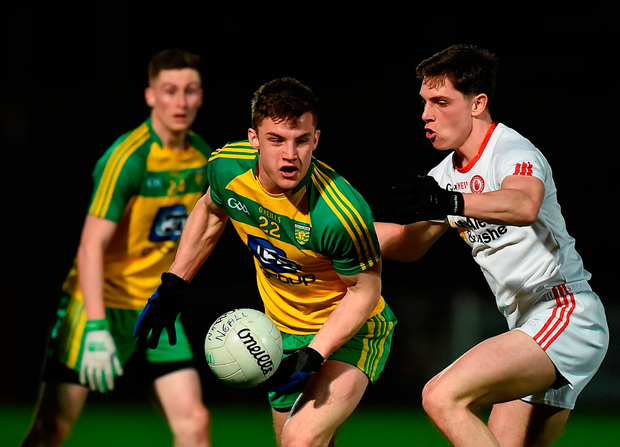 Tony McCleneghan of Donegal eyes up a pass as David Mulgrew of Tyrone applies pressure. Photo: Philip Fitzpatrick/Sportsfile