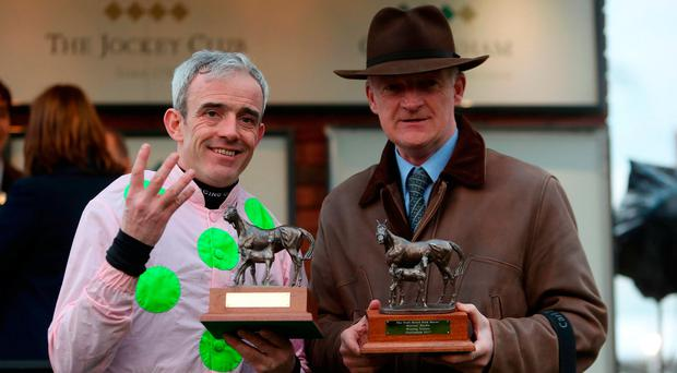 Jockey Ruby Walsh (left) and Trainer Willie Mullins (right) celebrate receiving trophies after winning the Trull House Stud Mares' Novices' Hurdle on Let's dance and achieving four wins during St Patrick's Thursday of the 2017 Cheltenham Festival. Photo: David Davies/PA Wire