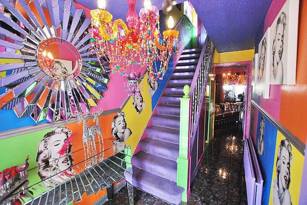 The home's entrance hall is a smack of bright colours which frame portraits of the late star