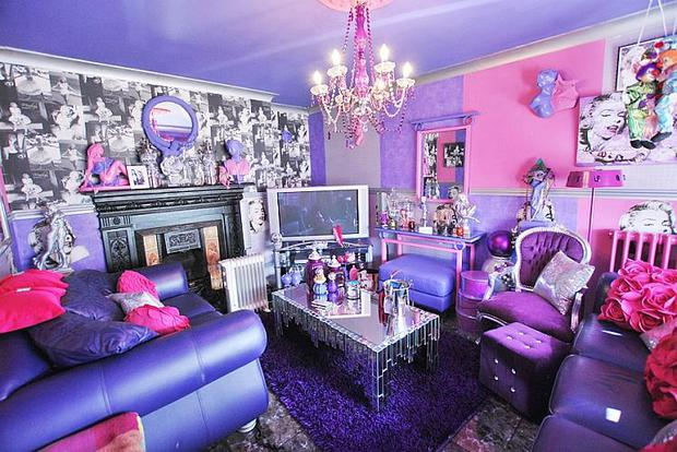 The purple-shaded sitting room is papered with some of Marilyn's most iconic photographs above the mantel