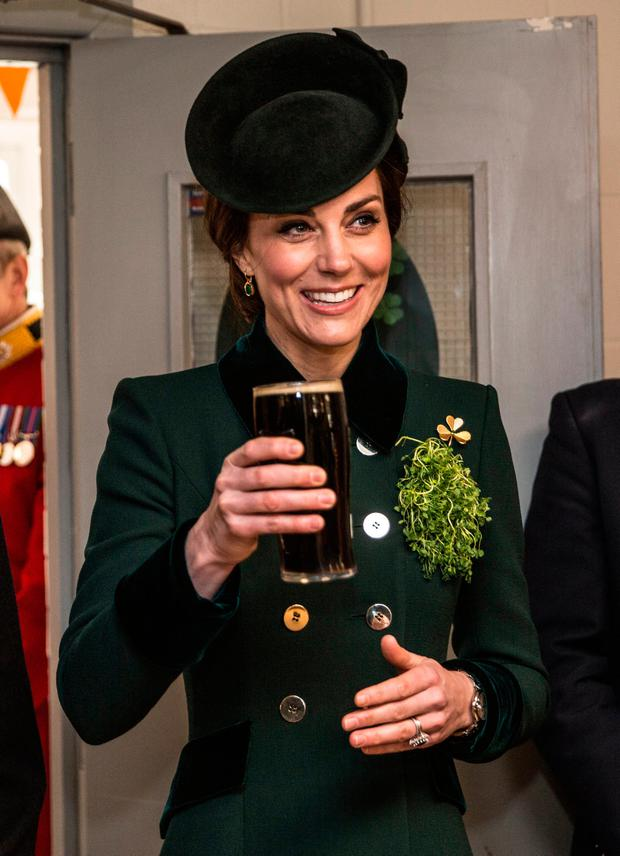 The Duchess of Cambridge takes a drink of Guinness as she meets with soldiers of the 1st Battalion Irish Guards in their canteen following their St Patrick's Day parade at Cavalry Barracks, Hounslow.