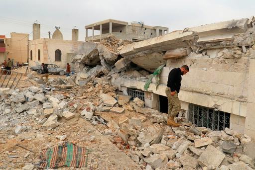 People inspect a damaged mosque after an airstrike on the rebel-held village of al-Jina. Photo: Reuters