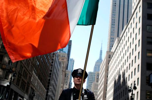 New York City correction officer Joseph Santos carries the Tricolour as he marches on 5th Avenue (REUTERS)