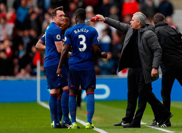 Manchester United's Eric Bailly is squirted with water by manager Jose Mourinho