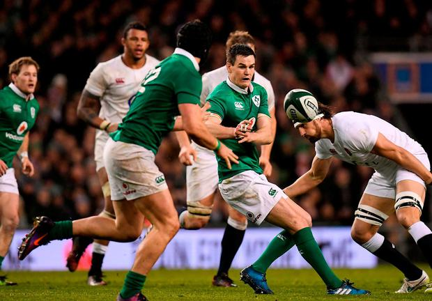 Tom Wood prepares to tackle Johnny Sexton as the Irish No 10 passes the ball. Photo: Brendan Moran/Sportsfile